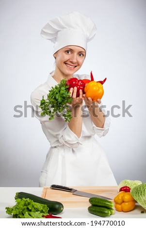 Happy young smiling female cook preparing vegetable salad
