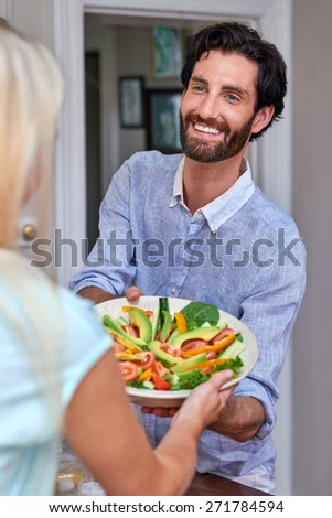Happy young smiling man helping in kitchen with salad bowl - stock photo