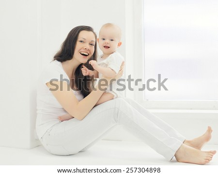 Happy young smiling mother with baby at home in white room near window - stock photo