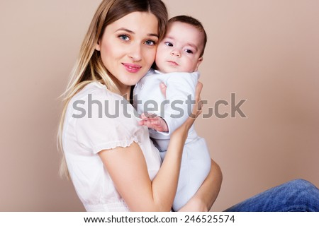 Happy young smiling mother with her little son - stock photo