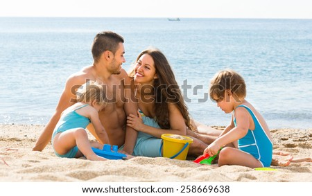 Happy young smiling parents with two kids resting at beach - stock photo