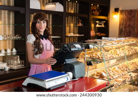 Happy young smiling seller in a cake shop - stock photo