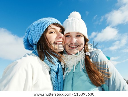 happy young smiling student people group in warm clothing lying on snow at winter outdoors - stock photo