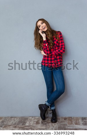 Happy young smiling woman in plaid shirt talking on mobile phone - stock photo
