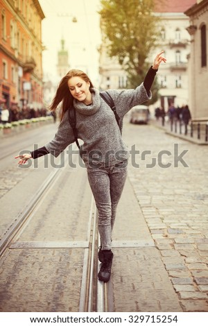 Happy young smiling woman walking on the railway