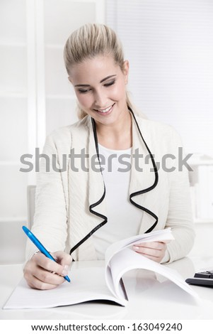 Happy young smiling woman working in a bank or insurance satisfied with his job sign a business letter. - stock photo
