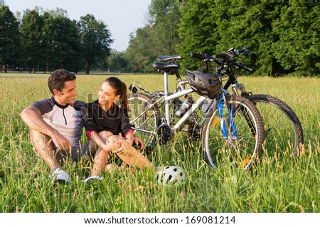 Happy Young Sportive Couple Sitting On Grass Besides Bicycles - stock photo