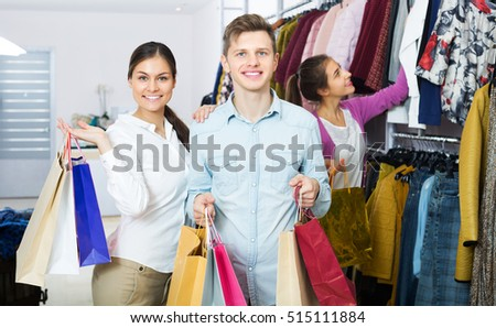 Happy young spouses carrying bags with purchases and smiling in boutique