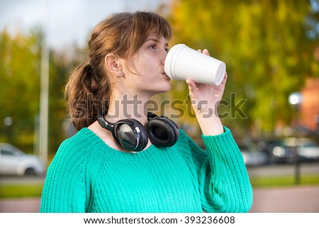 Happy young student girl drinking take away coffee. - stock photo
