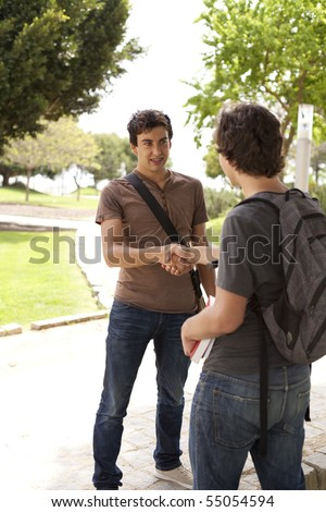 Happy young student giving a handshake to his classmate (selective focus) - stock photo