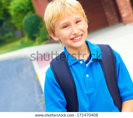 Happy young student going back to school carrying backpack. Cheerful school boy standing  in front of school building smiling and confident. Color Image, copy space. - stock photo