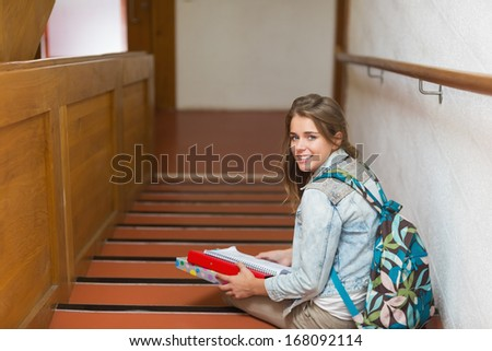 Happy young student sitting on stairs looking up at camera in college