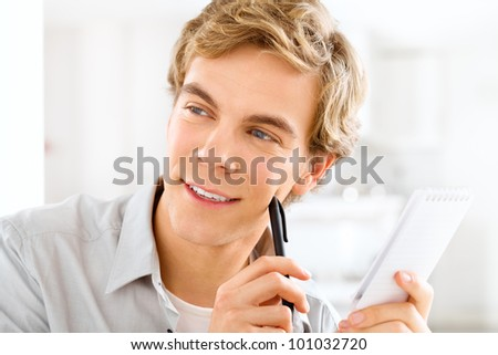 Happy young student studying at home holding pen