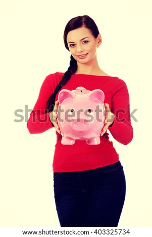 Happy young student woman holding piggybank - stock photo