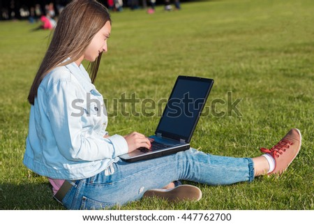 happy young student woman with laptop in city park  - stock photo