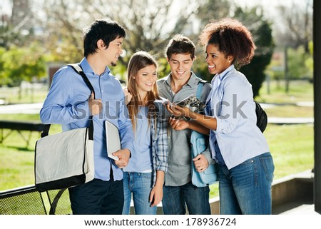 Happy young students discussing over book in university campus - stock photo