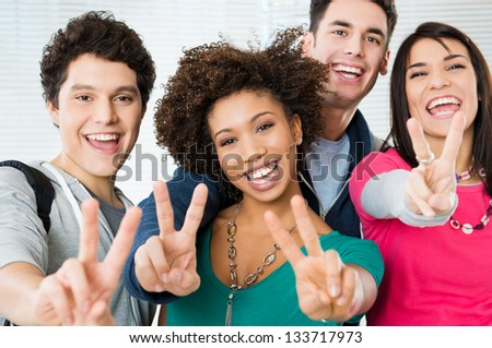 Happy Young students Showing Victory Sign