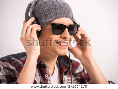 Happy young stylish man in sunglasses and headphones is smiling while standing against grey background. - stock photo