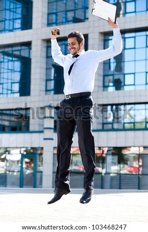Happy young successful businessman jumping against office building