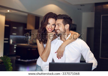 Happy young successful manager couple at home with laptop, confident people - stock photo