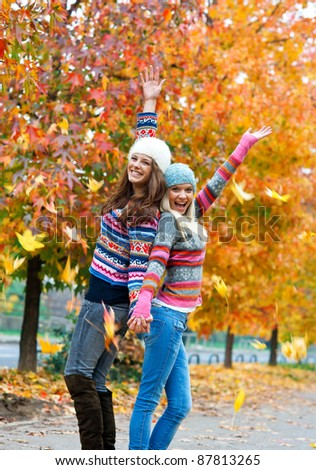happy young teen girls in autumn scenery throwing leaves