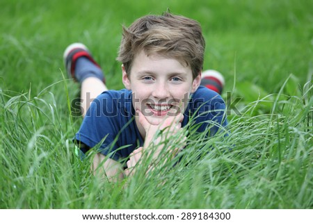 Happy young teenage boy lying in a meadow - stock photo