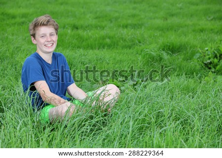 Happy young teenage boy sitting in a meadow - stock photo