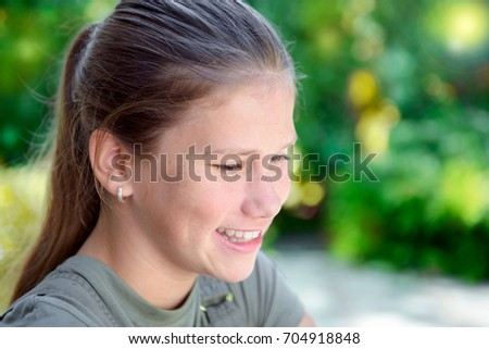 Happy young teenage girl smiling in the garden