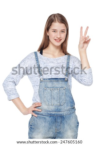 Happy young teenager girl showing victory gesture isolated on white background - stock photo
