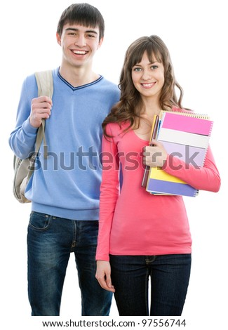 Happy young teenager students standing and smiling with books and bags - stock photo