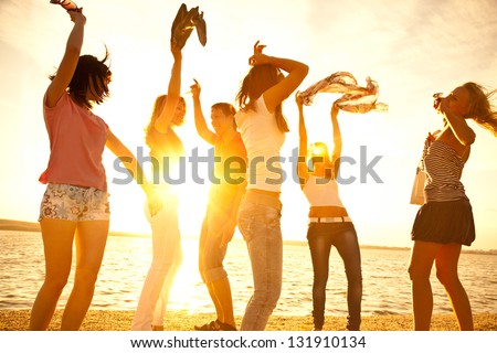 happy young teens dancing at the beach on  beautiful summer sunset