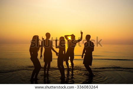 Happy young teens dancing at the beach on beautiful summer sunset - caucasian people