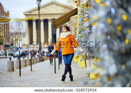 Happy young tourist in Paris on a winter day, Madeleine Church in the background - stock photo