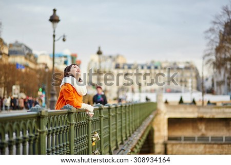 Happy young tourist in Paris on a winter day, near Notre-Dame cathedral - stock photo