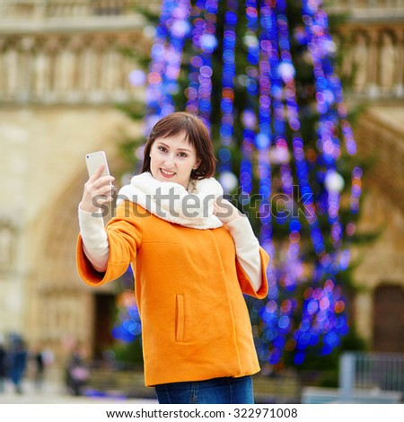 Happy young tourist in Paris on a winter day, taking selfie with main Parisian Christmas tree and Notre-Dame cathedral - stock photo