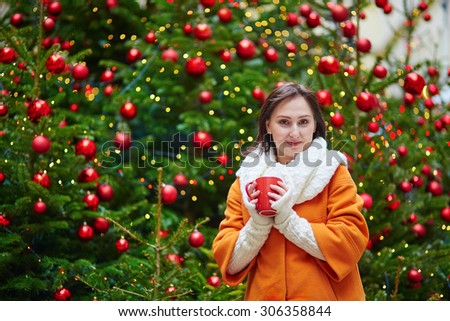 Happy young tourist in Paris on a winter day with cup of hot drink, decorated Christmas tree is in the background - stock photo