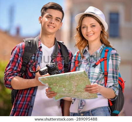 Happy young travelers sightseeing city with map. Eurotrip. - stock photo