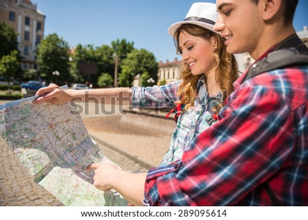 Happy young travelers sightseeing city with map. Side view. - stock photo