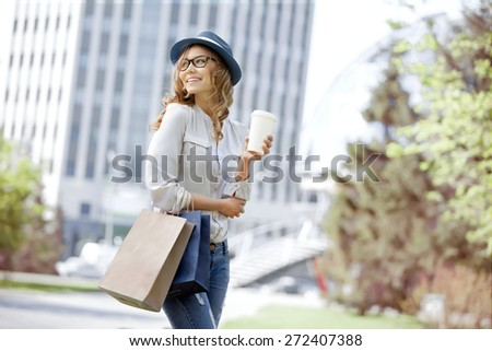 Happy young trendy woman drinking take away coffee and walking with shopping bags after shopping in an urban city. - stock photo