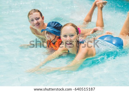Happy young two women And boy playing and having a good time at water fun park pool, on a summer hot day.
