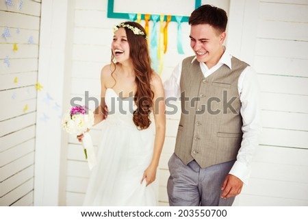 Happy young wedding couple, laughing and dancing. Vintage instagram effect. Selective focus on groom. - stock photo