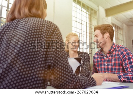 Happy Young White Couple Smiling to Each Other In Front of their Female Friend with Laptop Computer at the Table. - stock photo