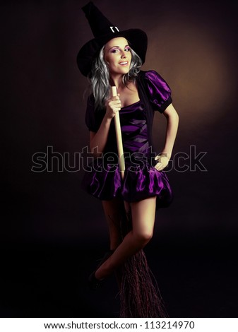happy young  witch with  a broom,  against yellow studio background - stock photo
