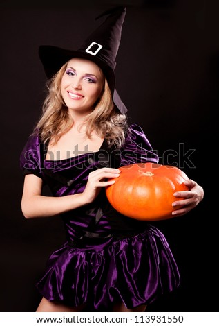 happy young witch with  a pumpkin,  against dark studio background
