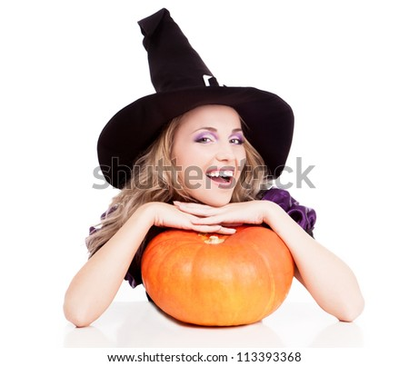 happy young witch with a pumpkin sitting by the table, isolated on white background - stock photo
