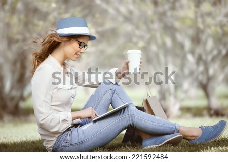 Happy young woman a disposable coffee cup sitting on the grass and using touch pad on her tablet in a summer park. - stock photo