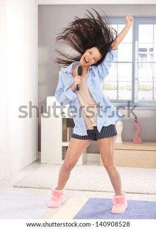 Happy young woman acting as pop star, using hairbrush as microphone, wearing pyjamas, long hair flying in the air. - stock photo