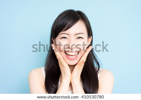 Happy young woman against blue background - stock photo