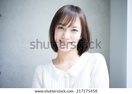 happy young woman against concrete wall