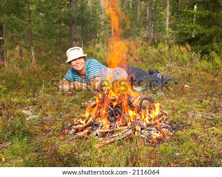 Happy young woman and campfire - stock photo